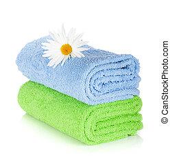 Toallas azules y verdes y flor de manzanilla