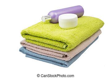 Toallas de verde rosa azul con champú y crema