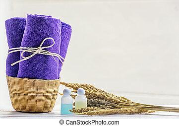Toallas púrpura en cesta de mimbre con jabón líquido.