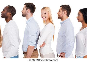 Todos tendrán una oportunidad. Una vista lateral de una hermosa joven mirando a la cámara y sonriendo mientras estaba de pie en una fila con otras personas y contra fondo blanco