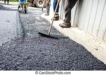 Trabajador con herramientas especiales trabajando con asfalto fresco y bitumen