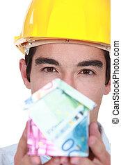 Trabajador de construcción que tiene la casa hecha de dinero