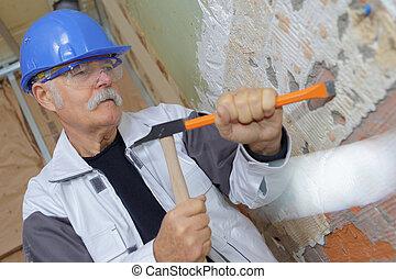 Trabajador de construcción senior con un cincel y un martillo