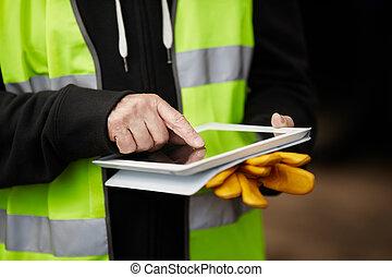 Trabajador de construcción usando pastillas digitales
