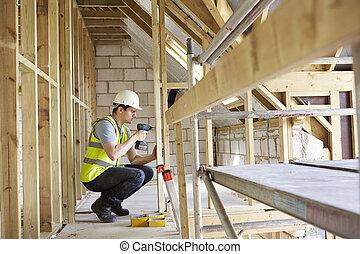 Trabajador de construcción usando taladro en construcción de casas