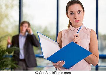 Trabajador de oficina sosteniendo carpeta azul