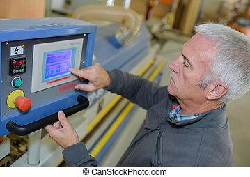 Trabajador en el taller operando máquina de ponche por ordenador