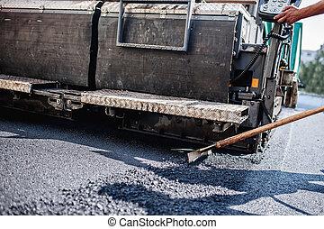 Trabajador masculino operando máquinas de asfalto en construcción
