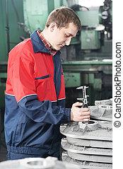 Trabajador midiendo herramientas de detalle