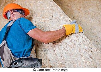 Trabajador moviendo tablas de madera contrachapada