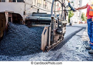 Trabajador o ingeniero operando una máquina de pavimento