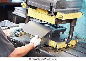 Trabajador operando la máquina de prensa de hoja de metal