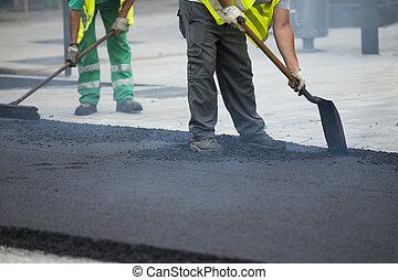 Trabajador operando máquina de asfalto asfalto durante la construcción de carreteras