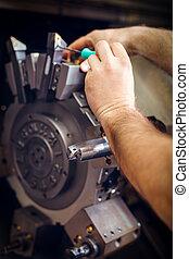 Trabajador trabajando con la máquina CNC