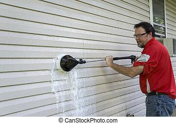 Trabajador usando un cepillo de alta presión para limpiar algas y moho del revestimiento de vinilo