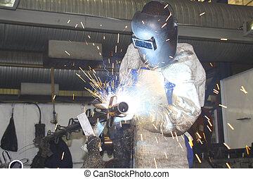 Trabajador y trabajador soldando un componente metal