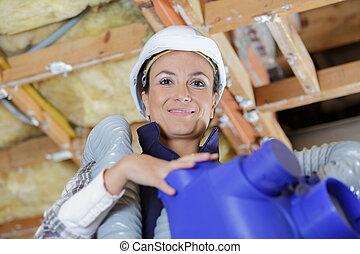 Trabajadora de construcción femenina instalando un nuevo sistema de ventilación