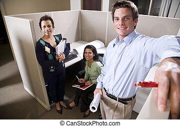 Trabajadores de oficinas reunidos en un cubículo