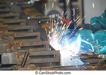 Trabajadores soldando piezas en una línea de producción