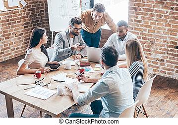 Trabajando en equipo. Un grupo de seis jóvenes discutiendo algo y gestando mientras están sentados en la mesa en la oficina