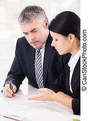 Trabajando en proyecto juntos. Dos personas de negocios seguras discutiendo algo mientras están sentados juntos en la mesa