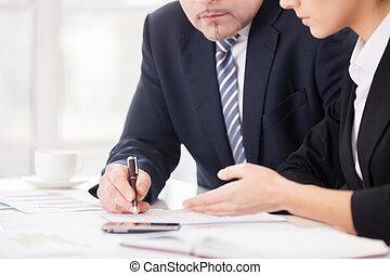 Trabajo en equipo. Una imagen de dos personas de negocios seguras discutiendo algo mientras se sentaban juntos en la mesa