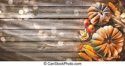 Trasfondo de Acción de Gracias con calabazas y hojas cayendo en una mesa de madera rústica