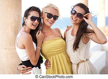 Tres adorables mujeres con gafas de sol