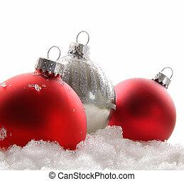 Tres bolas de Navidad rojas en la nieve