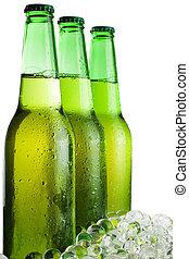 Tres botellas de cerveza verdes con hielo aislado sobre fondo blanco
