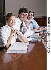 Tres empleados de oficinas trabajando en la sala de juntas