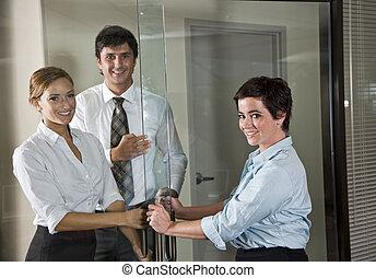 Tres empleados en la puerta de la sala de juntas