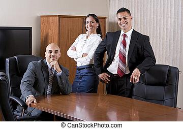 Tres empleados hispanos en la sala de juntas