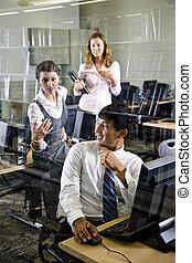 Tres estudiantes universitarios en la sala de computadoras de la biblioteca