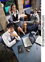 Tres jóvenes obreros trabajando en la sala de reuniones