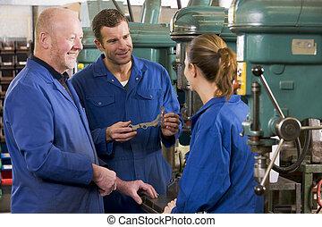 Tres maquinistas en el espacio de trabajo por máquina hablando