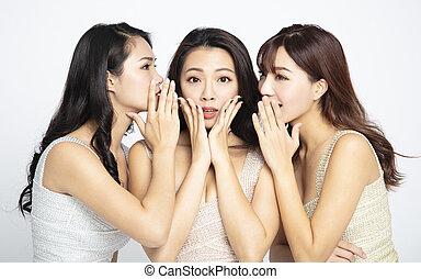 Tres mujeres asiáticas contándole susurros y chismes secretos