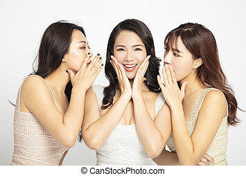 Tres mujeres contándole susurros y chismes secretos