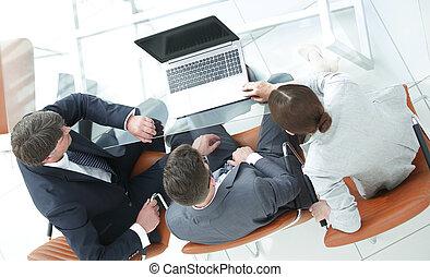 Tres personas de negocios, reuniéndose alrededor de una mesa de juntas