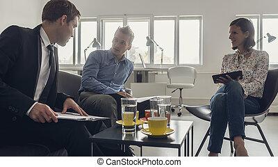 Tres personas de negocios sentadas alrededor de una mesa de café