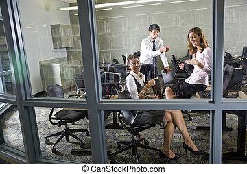 Tres profesores reunidos en la sala de computadoras de la biblioteca