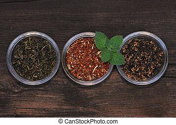Tres tazas con hojas de té variadas