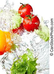 Tres tomates rojos frescos, pimienta amarilla y lechuga en agua salpicada, aislados en el fondo blanco