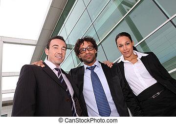 Trio de negocios fuera de un edificio de oficinas