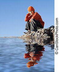 Triste niño deprimido sentado solo al aire libre