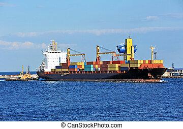 Tugboat asistiendo al carguero de carga