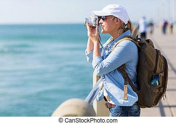 Turística femenina tomando fotos en el muelle