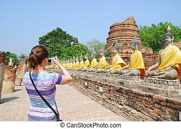 Turista con cámara frente a estatuas de Buda