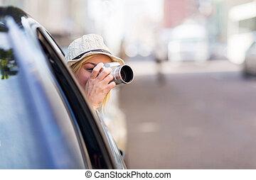 Turista dentro de un coche tomando fotos