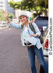 Turista llamando a un taxi en la calle